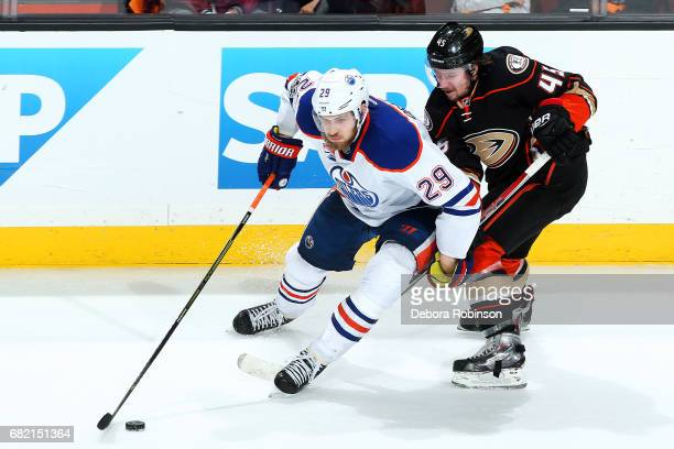 Leon Draisaitl of the Edmonton Oilers skates with the puck with pressure from Sami Vatanen of the Anaheim Ducks in Game Five of the Western...