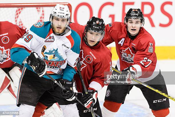 Leon Draisaitl of the Kelowna Rockets battles for position with Raphael Maheux and Ryan Graves of the Quebec Remparts in Game One during the 2015...