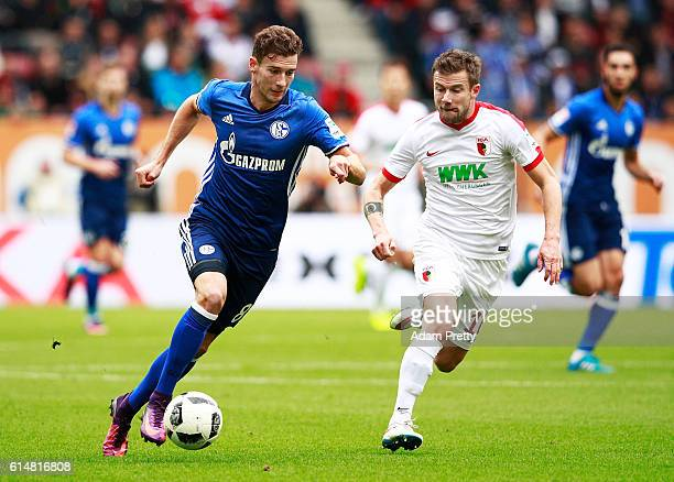 Leon Goretzka of Schalke 04 is challenged by Daniel Baier of Augsburg during the Bundesliga match between FC Augsburg and FC Schalke 04 at WWK Arena...