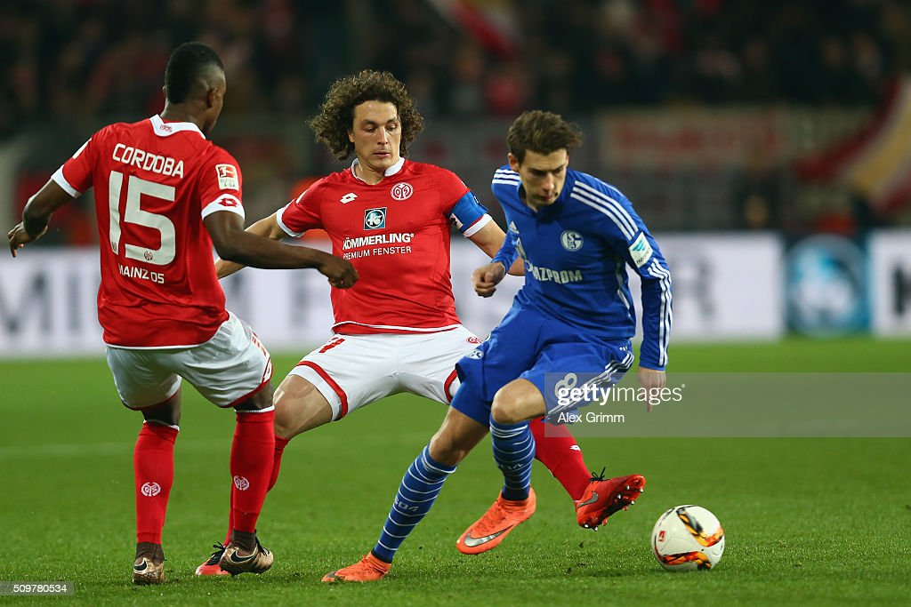 Leon Goretzka of Schalke is challenged by <a gi-track='captionPersonalityLinkClicked' href=/galleries/search?phrase=Julian+Baumgartlinger&family=editorial&specificpeople=4228877 ng-click='$event.stopPropagation()'>Julian Baumgartlinger</a> and Jhon Cordoba (R-L) of Mainz during the Bundesliga match between 1. FSV Mainz 05 and FC Schalke 04 at Coface Arena on February 12, 2016 in Mainz, Germany.