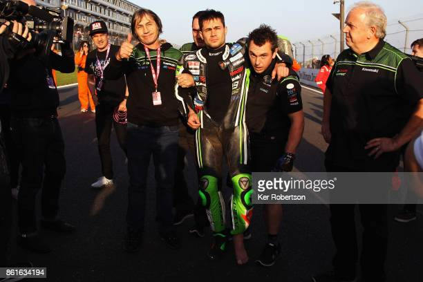 Leon Haslam of JG Speedfit Kawasaki team is helped onto the track by a mechanic and his father Ron Haslam to congratulate Shane Byine of Be Wiser...