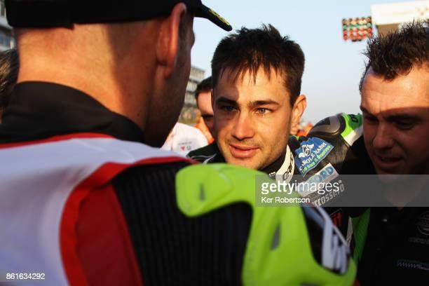 Leon Haslam of JG Speedfit Kawasaki team is helped onto the track to congratulate Shane Byine of Be Wiser Ducati on winning the British Superbike...