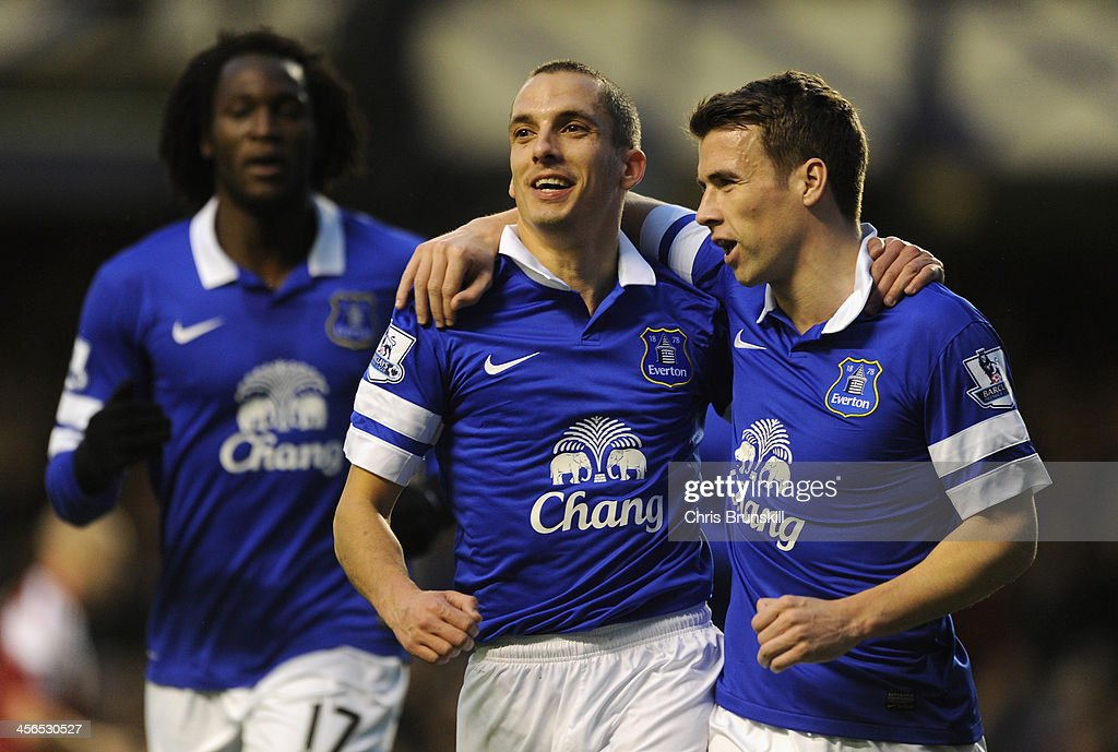 Leon Osman of Everton celebrates scoring the opening goal with team-mate Seamus Coleman (r) during the Barclays Premier League match between Everton and Fulham at Goodison Park on December 14, 2013 in Liverpool, England.