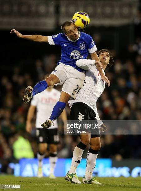Leon Osman of Everton wins the ball ahead of Bryan Ruiz of Fulham during the Barclays Premier League match between Fulham and Everton at Craven...