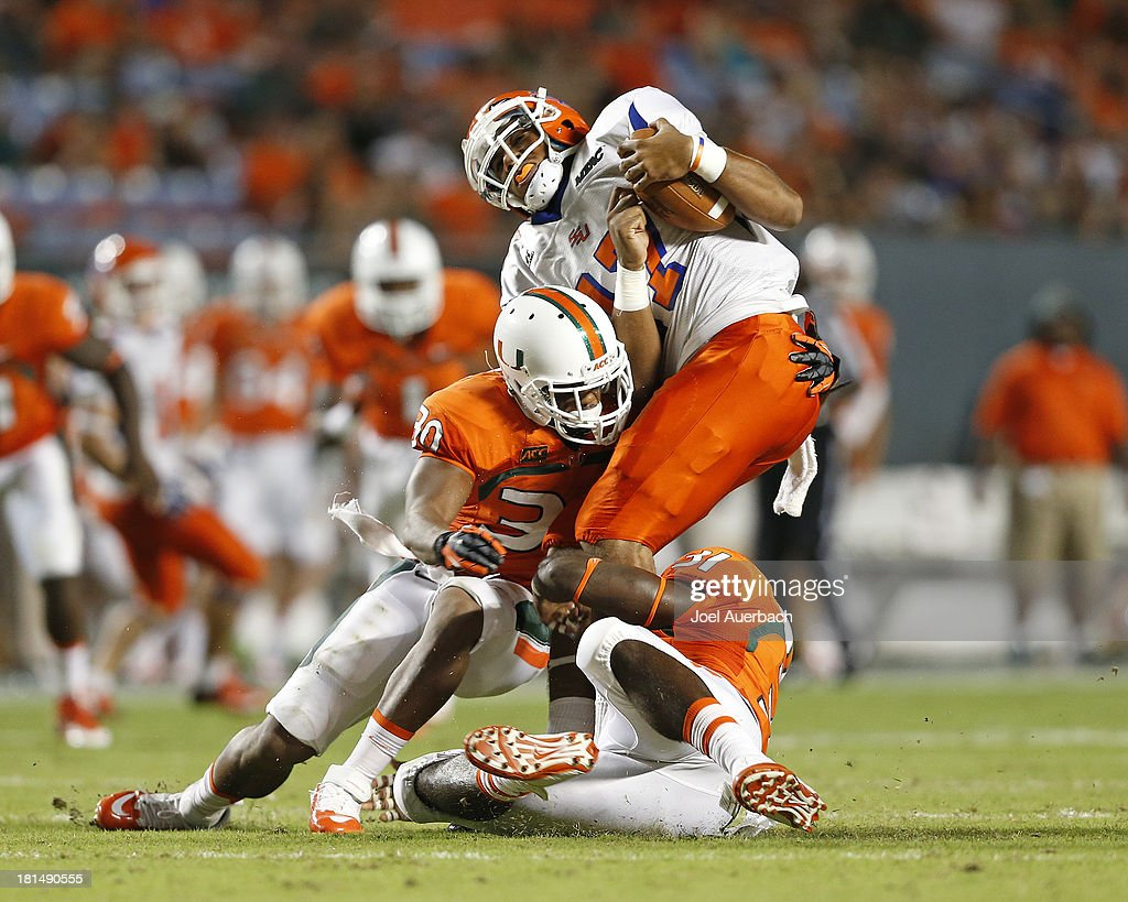 Leon Prunty #17 of the Savannah State Tigers is tackled by A.J. Highsmith #30 and Tyrone Cornileus #31 of the Miami Hurricanes on September 21, 2013 at Sun Life Stadium in Miami Gardens, Florida.