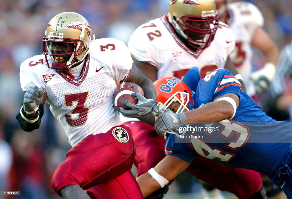Leon Washington of the Florida State Seminoles runs the ball upfield as Matt Farrior of the Florida Gators defends during the game on November 29...