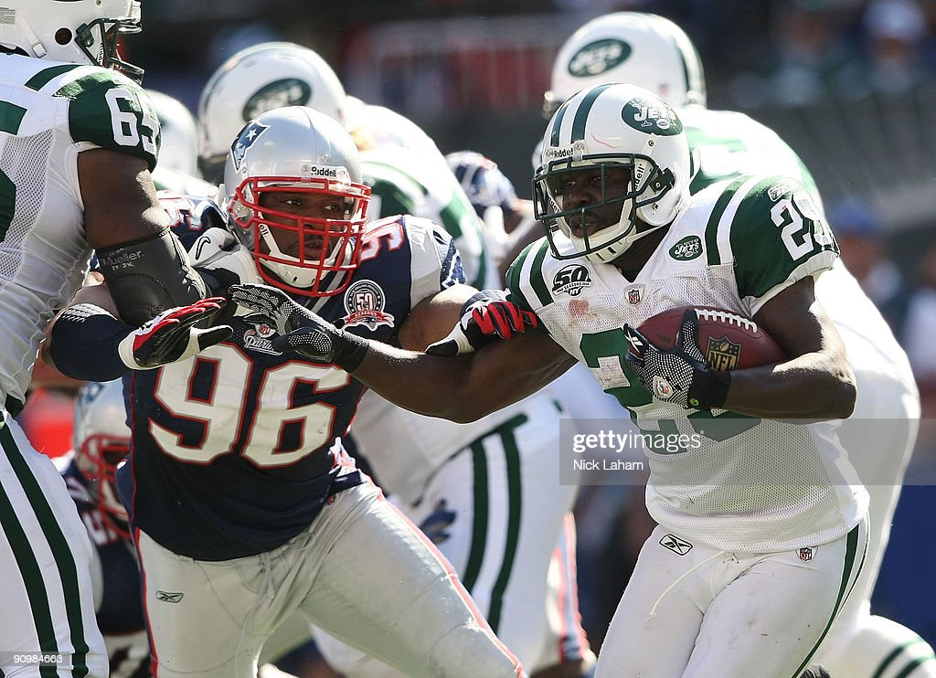 Leon Washington of the New York Jets runs the ball under pressure from the tackle of Adalius Thomas of the New England Patriots at Giants Stadium on...