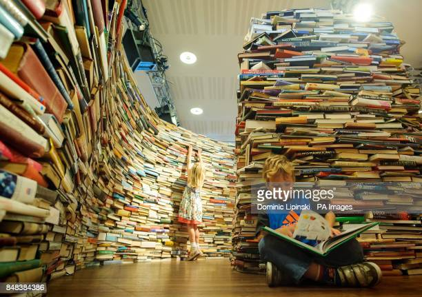 Leona and Charlie Ryan from Norfolk explore the 'aMAZEme' installation a maze constructed of 250000 books by Brazilian artists Marcos Saboya and...