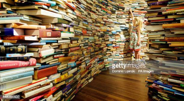 Leona Ryan from Norfolk explores the 'aMAZEme' installation a maze constructed of 250000 books by Brazilian artists Marcos Saboya and Gualter Pupo at...
