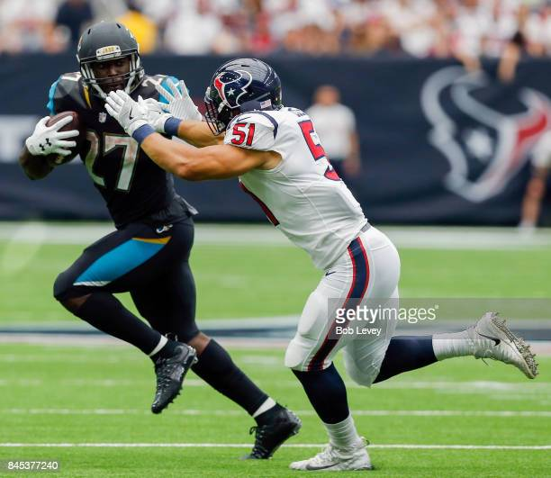 Leonard Fournette of the Jacksonville Jaguars holds off Dylan Cole of the Houston Texans as he rushes in the fourth quarter at NRG Stadium on...