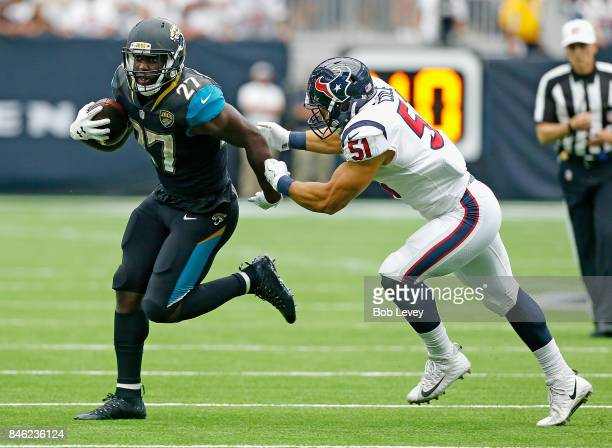 Leonard Fournette of the Jacksonville Jaguars holds off the tackle attempt by Dylan Cole of the Houston Texans at NRG Stadium on September 10 2017 in...