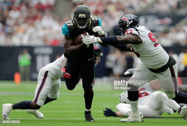 Leonard Fournette of the Jacksonville Jaguars is tackled by Johnathan Joseph and Joel Heath of the Houston Texans in the first quarter at NRG Stadium...