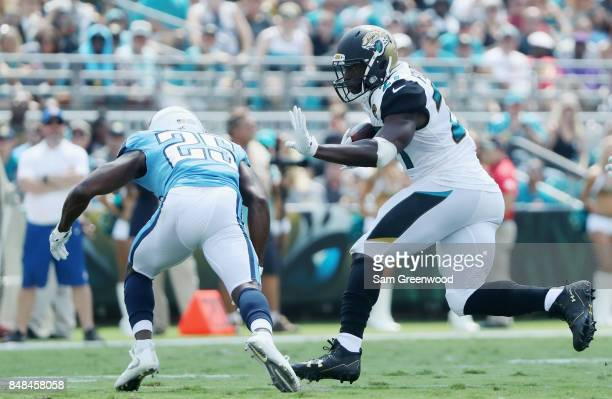 Leonard Fournette of the Jacksonville Jaguars runs with the football against Adoree' Jackson of the Tennessee Titans during the first half of their...