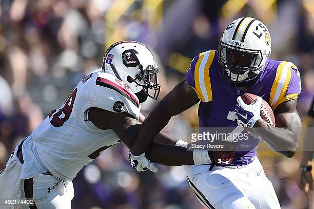 Leonard Fournette of the LSU Tigers avoids a tackle by Jonathan Walton of the South Carolina Gamecocks during the first quarter of a game at Tiger...