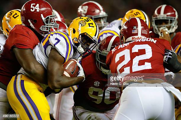 Leonard Fournette of the LSU Tigers is tackled by Dalvin Tomlinson Jarren Reed and Ryan Anderson of the Alabama Crimson Tide in the third quarter at...