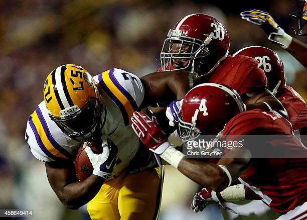 Leonard Fournette of the LSU Tigers is tackled by Denzel Devall and Eddie Jackson of the Alabama Crimson Tide during a game at Tiger Stadium on...