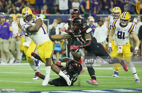 Leonard Fournette of the LSU Tigers runs with the ball as he gets tackeled by Micah Awe of the Texas Tech Red Raiders during the second half of the...