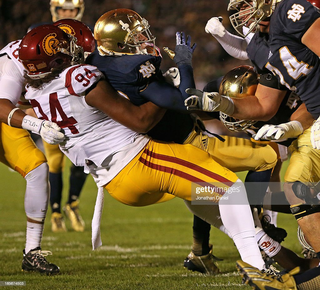 Leonard Williams #94 of the University of Southern California Trojans drops Cam McDaniel #33 of the Notre Dame Fighting Irish at Notre Dame Stadium on October 19, 2013 in South Bend, Indiana.