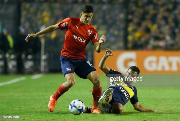 Leonardo Jara of Boca Juniors fights for the ball with Gaston Togni of Independiente during a match between Boca Juniors and Independiente as part of...