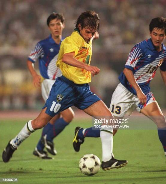 Leonardo of Brazil prepares to kick the ball to score a goal and give his team a 41 lead over Japan as Japanese defendersMotohiro Yamaguchi and...