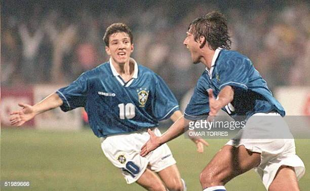 Leonardo of Brazil runs to his teammate Juninho as they celebrate Leonardo's goal scored in early action of their 13 July Copa America soccer match...