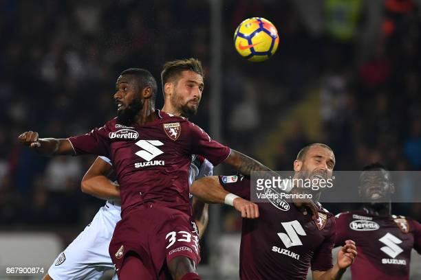 Leonardo Pavoletti of Cagliari Calcio clashes with Nicolas N koulou and Lorenzo De Silvestri of Torino FC during the Serie A match between Torino FC...