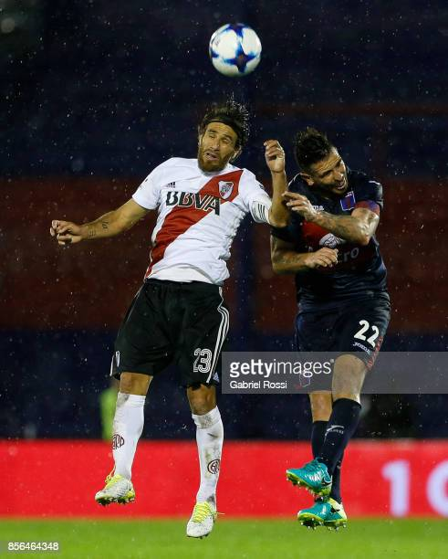 Leonardo Ponzio of River Plate and Denis Stracqualursi of Tigre jump for a header during a match between Tigre and River Plate as part of Superliga...
