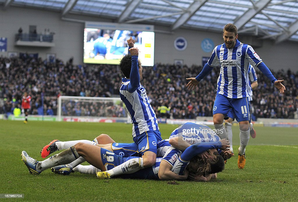 Leonardo Ulloa of Brighton & Hove Albion is mobbed by his team mates after scoring his hatrick during the npower Championship match between Brighton & Hove Albion and Huddersfield Town at The Amex Stadium on March 02, 2013 in Brighton England.