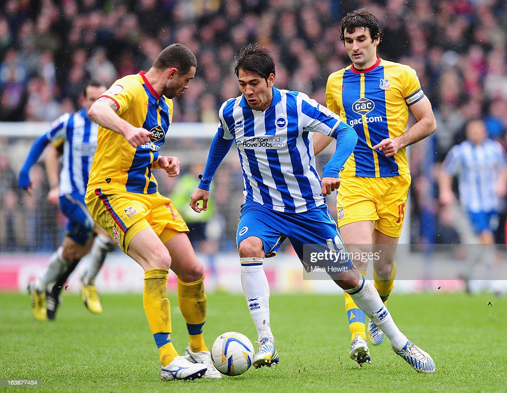 Leonardo Ulloa of Brighton skips past Damien Delaney during the npower Championship match between Brighton & Hove Albion and Crystal Palace at Amex Stadium on March 17, 2013 in Brighton, England.