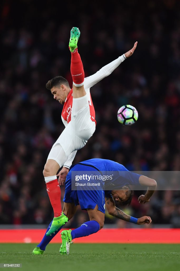 Leonardo Ulloa of Leicester City and Gabriel of Arsenal clash during the Premier League match between Arsenal and Leicester City at the Emirates Stadium on April 26, 2017 in London, England.