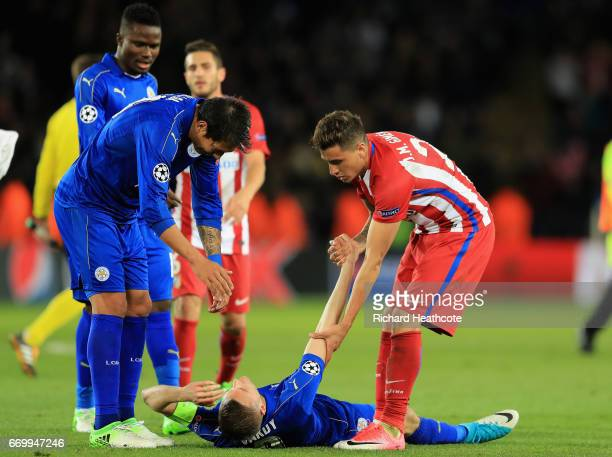 Leonardo Ulloa of Leicester City and Jose Gimenez of Atletico Madrid help up Jamie Vardy of Leicester City after the UEFA Champions League Quarter...