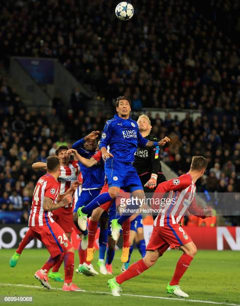 Leonardo Ulloa of Leicester City and Kasper Schmeichel of Leicester City attempt to head the ball during the UEFA Champions League Quarter Final...