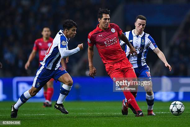 Leonardo Ulloa of Leicester City FC competes for the ball with Oliver Torres and Diogo Jota of FC Porto during the UEFA Champions League match...