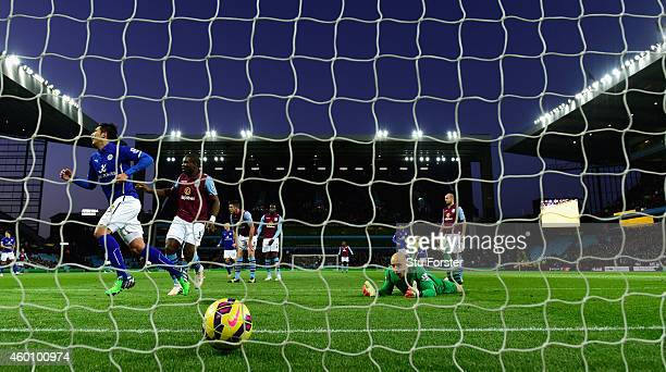 Leonardo Ulloa of Leicester scores the first goal past Villa goalkeeper Brad Guzan during the Barclays Premier League match between Aston Villa and...