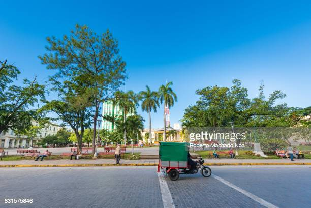 Leoncio Vidal plaza Cuban National Monument Small green auto rickshaw passing down broad paved road with trees benches buildings and deep blue sky