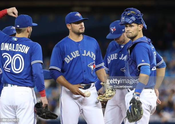 Leonel Campos of the Toronto Blue Jays looks on moments before being relieved as Luke Maile looks on in the seventh inning during MLB game action...