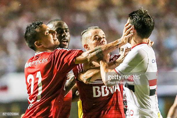 Leonel Vangioni and Andres D'Alessandro of River Plate scuffle with Jonathan Calleri Sao Paulo during a match between Sao Paulo and River Plate as...