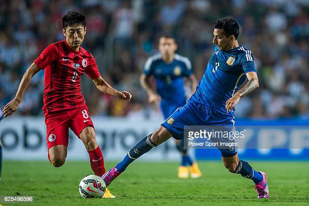 Leonel Vangioni of Argentina competes for the ball with Deshuai Xu of Hong Kong during the HKFA Centennial Celebration Match between Hong Kong and...