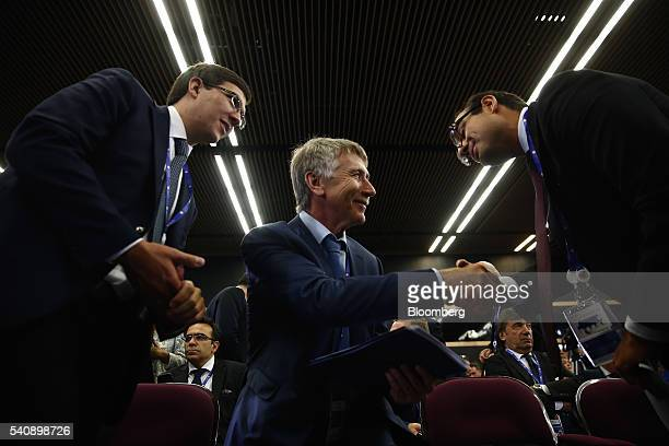 Leonid Mikhelson billionaire and chairman of OAO Novatek center greets an attendee during a panel session on day two of the St Petersburg...