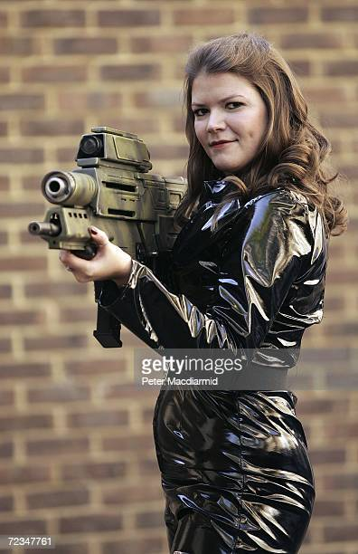 Leonie Ashfield from Christie's auctioneers poses with a prop tank buster gun from 'Die Another Day' during promotion of a sale of weapons from James...