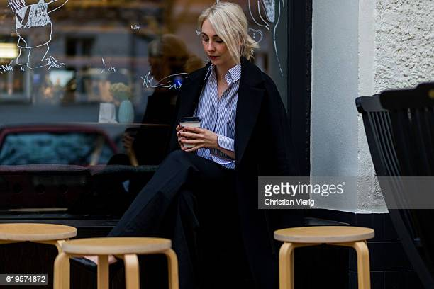 Leonie Markhorst sitting in a cafe and holding a coffee to go in her hands wears a black coat COS a blue white stripped button shirt from Avelon...