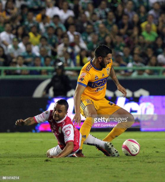 Leon's footballer Luis Montes falls next to Tigres' French Andre Gignac during their Mexican Apertura tournament match at the Nou Camp stadium in...