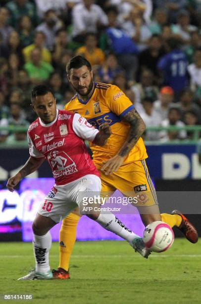 Leon's footballer Luis Montes is marked by Tigres' French Andre Gignac during their Mexican Apertura tournament match at the Nou Camp stadium in Leon...