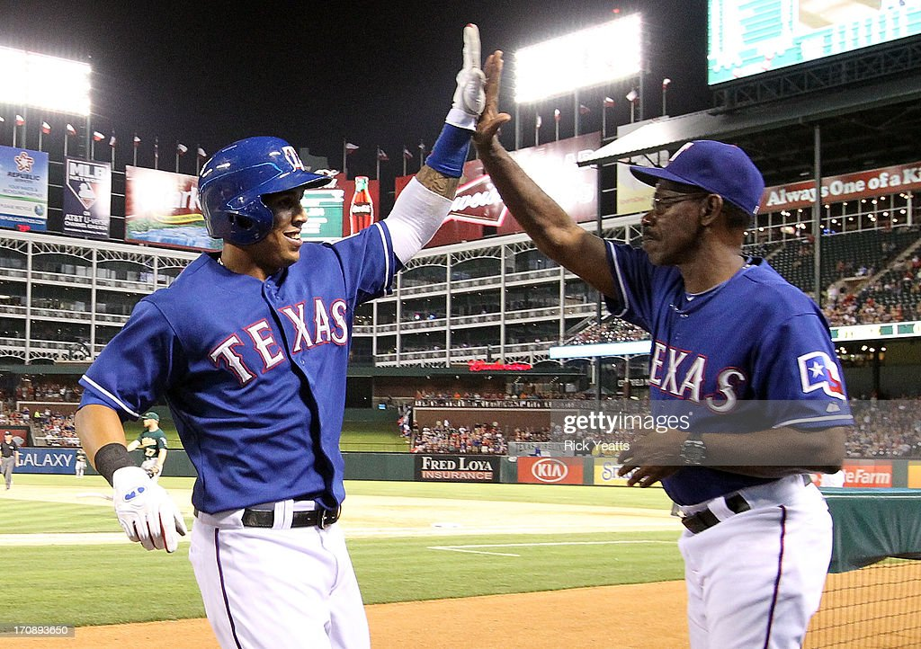 Leonys Martin #2 is congratulated by Ron Washington #38 of the Texas Rangers for scoring against the Oakland Athletics on a hit by Nelson Cruz at Rangers Ballpark in Arlington on June 19, 2013 in Arlington, Texas.