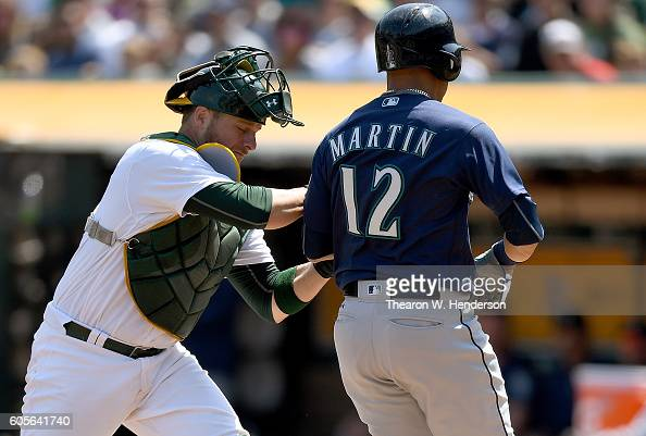 Leonys Martin of the Seattle Mariners is caught in a rundown is tagged out at home plate by Stephen Vogt of the Oakland Athletics in the top of the...
