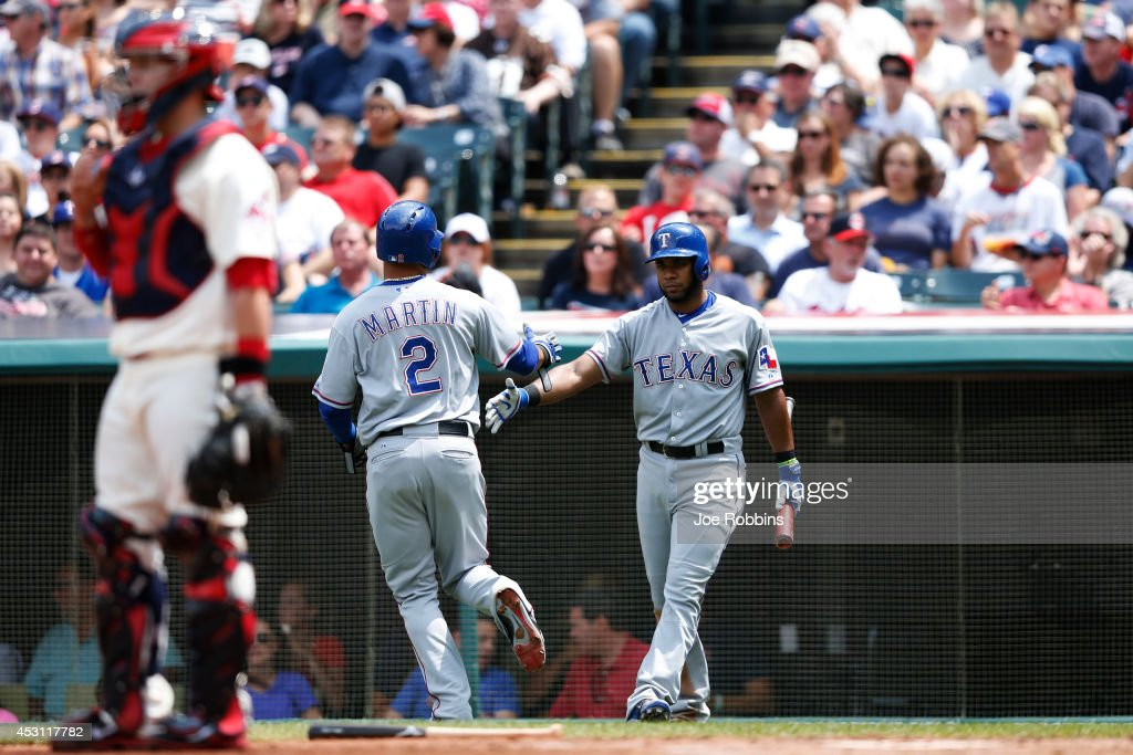 Leonys Martin #2 of the Texas Rangers is congratulated by <a gi-track='captionPersonalityLinkClicked' href=/galleries/search?phrase=Elvis+Andrus&family=editorial&specificpeople=4845974 ng-click='$event.stopPropagation()'>Elvis Andrus</a> #1 after scoring a run on a sacrifice fly by Shin-Soo Choo in the second inning of the game against the Cleveland Indians at Progressive Field on August 3, 2014 in Cleveland, Ohio.