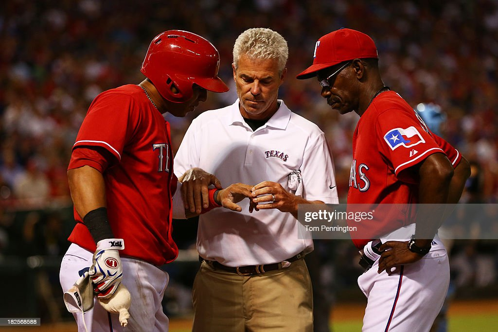 Leonys Martin #2 of the Texas Rangers receives medical attention after being hit by a foul ball as manager <a gi-track='captionPersonalityLinkClicked' href=/galleries/search?phrase=Ron+Washington&family=editorial&specificpeople=225012 ng-click='$event.stopPropagation()'>Ron Washington</a> #38 looks on during the American League Wild Card tiebreaker game against the Tampa Bay Rays at Rangers Ballpark in Arlington on September 30, 2013 in Arlington, Texas.