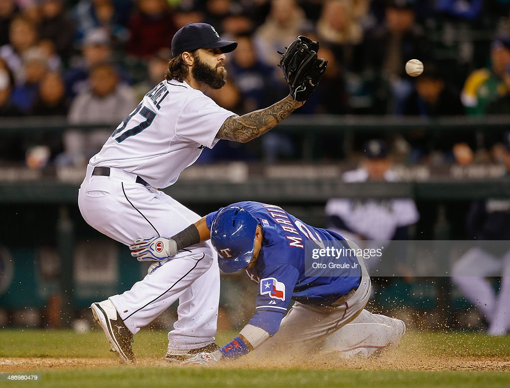 Leonys Martin #2 of the Texas Rangers scores on a wild pitch by relief pitcher <a gi-track='captionPersonalityLinkClicked' href=/galleries/search?phrase=Joe+Beimel&family=editorial&specificpeople=567158 ng-click='$event.stopPropagation()'>Joe Beimel</a> #97 of the Seattle Mariners as he waits to take the throw from catcher Mike Zunino in the ninth inning at Safeco Field on April 26, 2014 in Seattle, Washington.