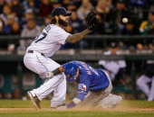 Leonys Martin of the Texas Rangers scores on a wild pitch by relief pitcher Joe Beimel of the Seattle Mariners as he waits to take the throw from...