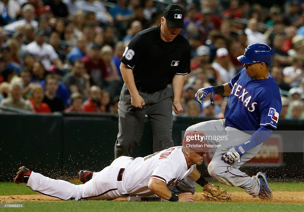 Leonys Martin #2 of the Texas Rangers slides into infielder <a gi-track='captionPersonalityLinkClicked' href=/galleries/search?phrase=Cliff+Pennington+-+Baseball+Player&family=editorial&specificpeople=8134145 ng-click='$event.stopPropagation()'>Cliff Pennington</a> #4 of the Arizona Diamondbacks at third base during the eighth inning of the MLB game at Chase Field on April 21, 2015 in Phoenix, Arizona.